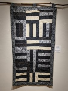 """Leanora E. Mims • <em>Say Her Name: Sunset, Brionna Taylor </em> • Gees Bend quilting pattern • 23½""""×43"""" • $850.00<a class=""""purchase"""" href=""""https://state-of-the-art-gallery.square.site/product/leanora-e-mims-sunset-quilted-wall-hanging/386"""" target=""""_blank"""">Buy</a>"""