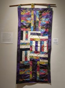 """Leanora E. Mims • <em>Say Her name: Sunrise, Sandra Bland</em> • Cross square quilting pattern • 23""""×48"""" • $950.00<a class=""""purchase"""" href=""""https://state-of-the-art-gallery.square.site/product/leanora-e-mims-sunrise-quilted-wall-hanging/385"""" target=""""_blank"""">Buy</a>"""