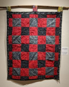 """Leanora E. Mims • <em>Say Her Name: We Will Remember Miriam Carey</em> • Cross square quilting pattern • 26½""""×43"""" • $800.00<a class=""""purchase"""" href=""""https://state-of-the-art-gallery.square.site/product/leanora-e-mims-say-her-name-we-will-remember-you/384"""" target=""""_blank"""">Buy</a>"""